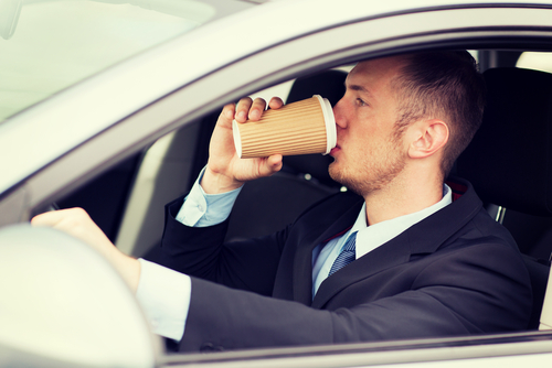 man drinking coffee behind the wheel of a car
