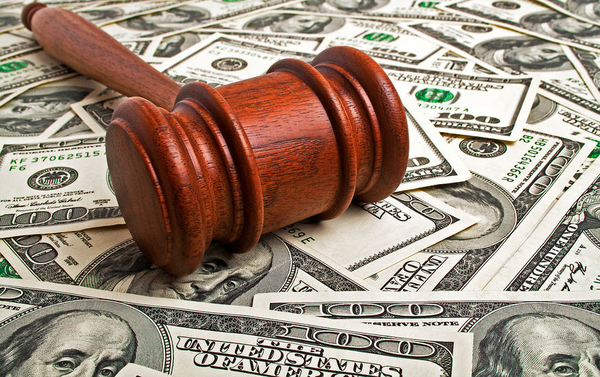 Judge's gavel laying on a pile of money